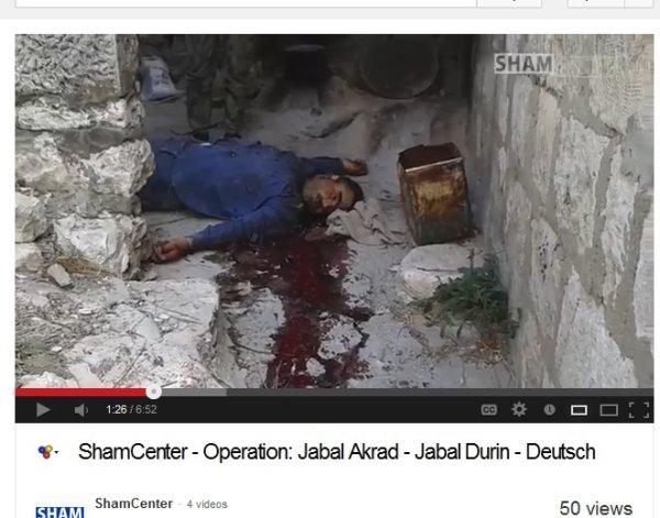 Das Opfer bekleidet mit blauer Hose und blauem Hemd. Sehr viel Blut zu sehen. Im Hintergrund Beine von einem Terroristen